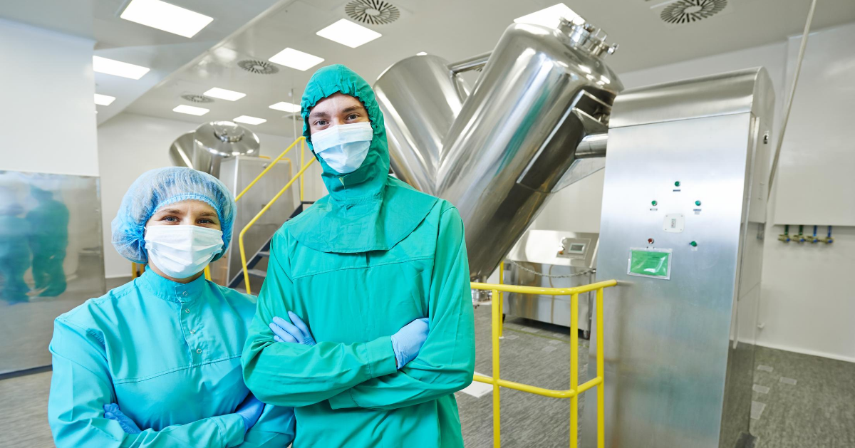 GMP Operators in Pharmaceutical Manufacturing Plant with V-Shaped Blenders