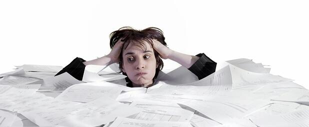 Person stressed by the volume of paper work to do