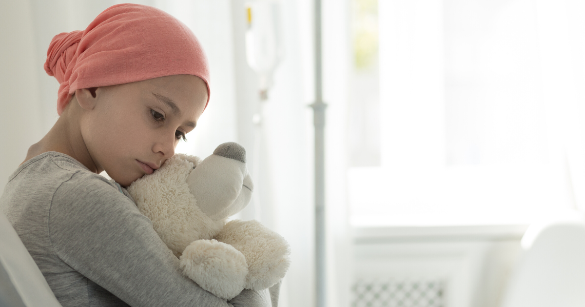 child cancer patient hugging a soft toy bear in hospital
